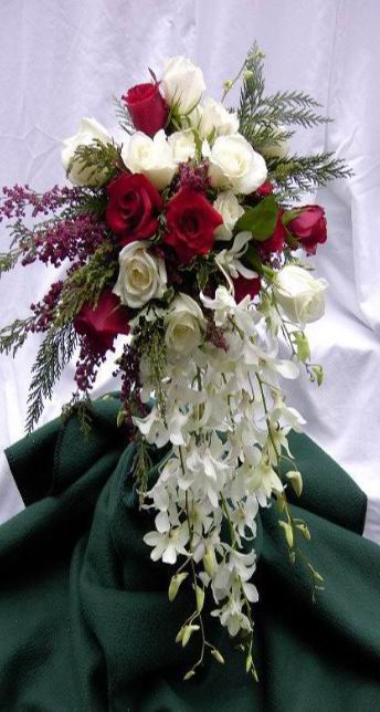 Red and White roses in basket with white orchids
