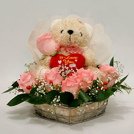 Teddy surrounded with with pink roses basket